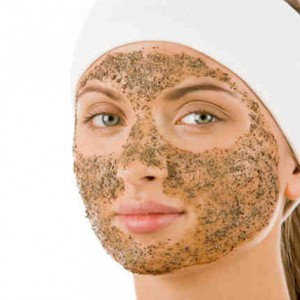 Beautiful woman with cleansing mask on her face looking at camera